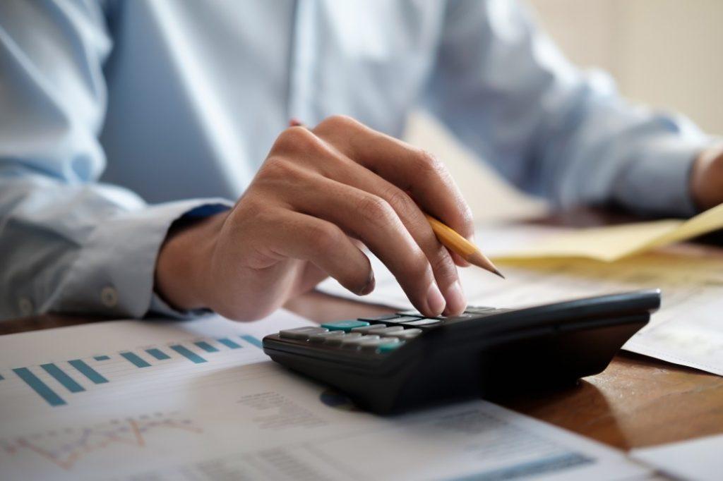 regime tributário - homem usando uma calculadora