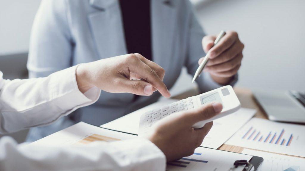 a importância do planejamento tributário - duas pessoas em uma reunião apontando para uma calculadora