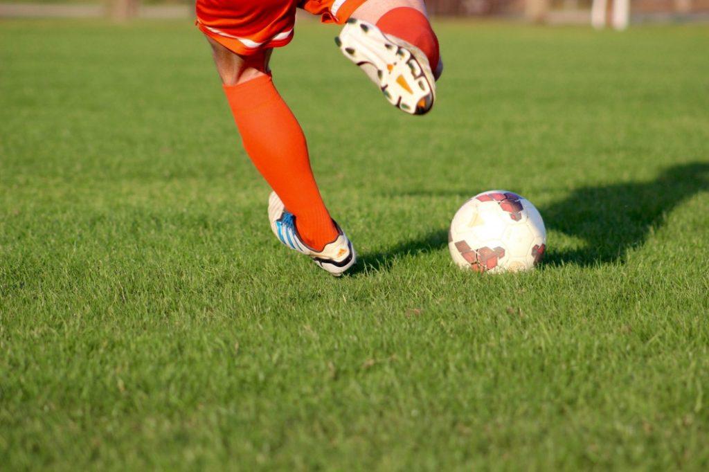 arbitragem desportiva - jogador de futebol chutando uma bola